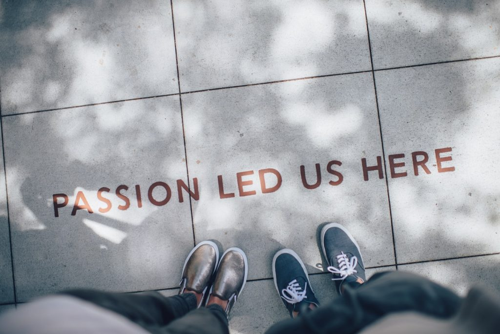 People looking down at their feet to the words Passion Led Us Here painted on the floor.
