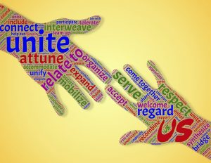 "Two hands reaching out to touch made up of a collection of words such as ""Come Together"" ""Us"" ""Unite"""